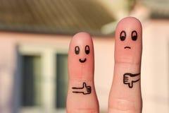 Τέχνη δάχτυλων του ζεύγους Η γυναίκα που παρουσιάζει τους αντίχειρες επάνω και παρουσίαση ανδρών φυλλομετρεί κάτω Στοκ εικόνες με δικαίωμα ελεύθερης χρήσης