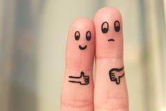 Τέχνη δάχτυλων του ζεύγους Η γυναίκα που παρουσιάζει τους αντίχειρες επάνω και παρουσίαση ανδρών φυλλομετρεί κάτω Στοκ φωτογραφία με δικαίωμα ελεύθερης χρήσης