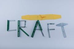 Τέχνη λέξης φιαγμένη από λεπτομέρειες κατασκευαστών μετάλλων στο άσπρο υπόβαθρο Στοκ Φωτογραφίες