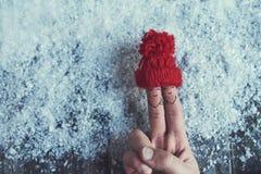 Τέχνη δάχτυλων του ζεύγους ερωτευμένη στο κόκκινο καπέλο πέρα από το υπόβαθρο χιονιού στοκ εικόνα με δικαίωμα ελεύθερης χρήσης