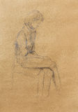 Τέχνη που επισύρει την προσοχή την όμορφη συνεδρίαση κοριτσιών σε μια καρέκλα και ένα άσπρο υπόβαθρο Στοκ Εικόνες