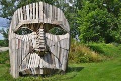 Τέχνη στη φύση - ξύλινο πρόσωπο μπροστά από πράσινο Στοκ Εικόνα