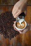 Τέχνη φλιτζανιών του καφέ latte που κάνει από το barista στο παλαιό ξύλινο backgrou στοκ εικόνες