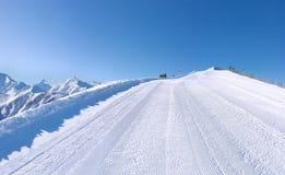 Τέλεια καλλωπισμένη κλίση σκι με τα βουνά Στοκ Φωτογραφία