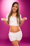 Τέλειο θηλυκό σώματος στη λευκιά εκμετάλλευση Barbells στοκ φωτογραφία