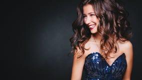 Τέλειο χαμόγελο έννοιας, διασκέδαση Οι νέες όμορφες σγουρές γυναίκες ακτινοβολούν μέσα φόρεμα στο σκοτεινό υπόβαθρο Copyspace Εορ Στοκ φωτογραφία με δικαίωμα ελεύθερης χρήσης