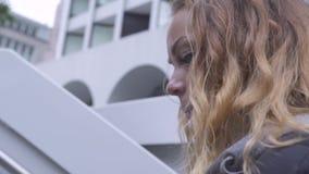 Τίναγμα να ανεβεί γυναικών προσώπου πυροβολισμού των νέων σκαλοπατιών στο σύγχρονο πάρκο πόλεων Κλείστε επάνω το σγουρό κοκκινομά απόθεμα βίντεο