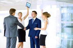 τίναγμα χεριών επιχειρημα&ta Δύο βέβαιοι επιχειρηματίες που τινάζουν τα χέρια και που χαμογελούν στεμένος στο γραφείο μαζί με Στοκ Εικόνα