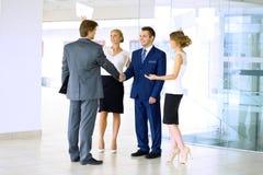 τίναγμα χεριών επιχειρημα&ta Δύο βέβαιοι επιχειρηματίες που τινάζουν τα χέρια και που χαμογελούν στεμένος στο γραφείο μαζί με Στοκ Φωτογραφία