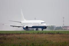 Τίτλος αεροπλάνων επιβατών στο διάδρομο με τις εκτεταμένες αεροτομές στη δυνατή βροχή στοκ εικόνες
