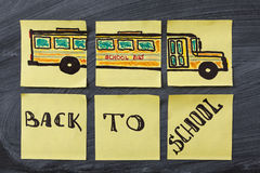 Τίτλοι πίσω στο σχολείο και το σχολικό λεωφορείο που γράφονται στα κίτρινα κομμάτια χαρτί στο μαύρο σχολικό πίνακα κιμωλίας Στοκ εικόνα με δικαίωμα ελεύθερης χρήσης