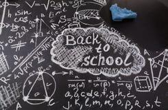 Τίτλος πίσω στο σχολείο, τύποι που γράφονται από την άσπρη κιμωλία στο μαύρο σχολικό πίνακα κιμωλίας και το μπλε κουρέλι για το σ στοκ φωτογραφία με δικαίωμα ελεύθερης χρήσης