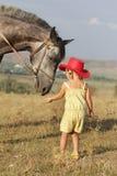 Ταΐζοντας άλογο κοριτσιών στη φυσική ανασκόπηση Στοκ εικόνα με δικαίωμα ελεύθερης χρήσης