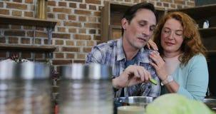Ταΐζοντας γυναίκα ανδρών με τα λαχανικά ευτυχές ζεύγος στο αγκάλιασμα κουζινών που εξετάζει μεταξύ τους φιλμ μικρού μήκους