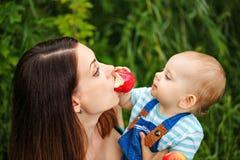 Ταΐζοντας μητέρα κορών ένα μήλο Στοκ Εικόνες
