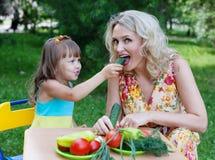 Ταΐζοντας μητέρα παιδιών παιδιών κορών κοριτσιών mum με το αγγούρι Στοκ εικόνα με δικαίωμα ελεύθερης χρήσης