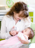 Ταΐζοντας μωρό μητέρων με τη σίτιση του μπουκαλιού στην κουζίνα Στοκ εικόνες με δικαίωμα ελεύθερης χρήσης