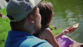 Ταΐζοντας πάπιες αγοριών και κοριτσιών εραστών από την ακτή στη λίμνη Οι εραστές ρίχνουν τα κομμάτια του ψωμιού στο νερό απόθεμα βίντεο