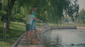 Ταΐζοντας πάπιες ζευγών Millennnial στη λίμνη στο πάρκο απόθεμα βίντεο