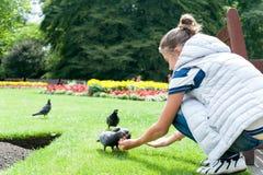 Ταΐζοντας περιστέρια νέων κοριτσιών το σκωτσέζικο καλοκαίρι πράσινο πάρκο Στοκ εικόνα με δικαίωμα ελεύθερης χρήσης
