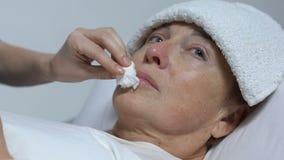Ταΐζοντας φωνάζοντας ηλικιωμένη γυναίκα νοσοκόμων με την πετσέτα στο μέτωπο, ανικανότητα μετά από την ασθένεια φιλμ μικρού μήκους