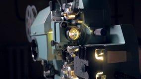 ταινία αριθμός ένα προβολέ&alph Το καμεραμάν ανάβει τον παλαιό προβολέα κινηματογράφων Μετακινηθείτε τον πυροβολισμό απόθεμα βίντεο