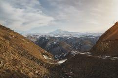 Ταινίες βουνοπλαγιών στα καυκάσια βουνά στο υπόβαθρο και το εκλείψας ηφαίστειο Elbrus ουρανού ηλιοβασιλέματος Στοκ φωτογραφία με δικαίωμα ελεύθερης χρήσης