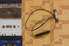 Ταινίες κασετών δίπλα στα ακουστικά bluetooth στοκ φωτογραφία με δικαίωμα ελεύθερης χρήσης