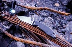 Τακτικοί μαχαίρι και φακός Μια φωτεινή φλόγα από το φανάρι Στοκ Φωτογραφία