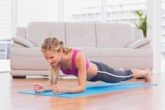 Τακτοποίηση ξανθή στη θέση σανίδων στο χαλί άσκησης Στοκ Φωτογραφίες
