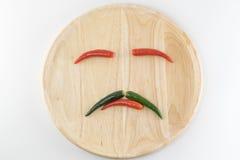 Τακτοποιήστε τα πιπέρια σε ένα ξύλινο πιάτο στοκ φωτογραφία
