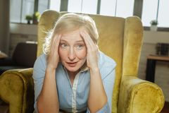 Τακτοποιήστε την ξανθή γυναίκα με τα μπλε μάτια που φορούν το μπλε πουκάμισο καθμένος στοκ εικόνες