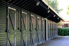 Τακτοποιημένη γραμμή πορτών στάβλων στο μακρύ πράσινο σταύλο Στοκ φωτογραφία με δικαίωμα ελεύθερης χρήσης