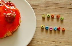 Τακτοποιημένη επιστολή ευτυχής λέξη της Κυριακής και κέικ φραουλών στο πιάτο Στοκ φωτογραφία με δικαίωμα ελεύθερης χρήσης