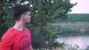 Τακτοποιημένος, μοντέρνος, ισχυρός τύπος το υπόβαθρο ενός πράσινου, όμορφου δέντρου, κοιτάζει στην άλλη πλευρά, ποταμός, φύση απόθεμα βίντεο