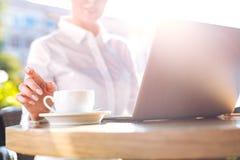 Τακτοποιημένο θηλυκό χέρι που φθάνει για ένα φλιτζάνι του καφέ στον καφέ στοκ φωτογραφία