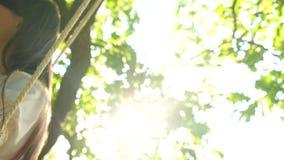 Ταλάντευση κοριτσιών στην ταλάντευση κάτω από ένα δρύινο δέντρο στον ήλιο, σε αργή κίνηση, κινηματογράφηση σε πρώτο πλάνο απόθεμα βίντεο