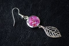 Ταλαντεύστε τα σκουλαρίκια φιαγμένα από εποξική ρητίνη και ξηρός αυξήθηκε πέταλα στοκ φωτογραφία