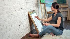 Ταλαντούχος γυναίκα ζωγράφος που κάνει τη γραφική εικόνα στον καμβά που χρησιμοποιεί τον πλήρη πυροβολισμό μολυβιών φιλμ μικρού μήκους