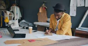 Ταλαντούχος σχεδιαστής μόδας που κάνει τις σημειώσεις στο σημειωματάριο που γράφει με το χαμόγελο μολυβιών απόθεμα βίντεο