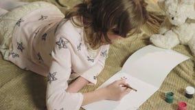 Ταλαντούχο κορίτσι που σύρει τακτοποιημένα με τα όμορφα λουλούδια γκουας στο λεύκωμά της, χόμπι απόθεμα βίντεο