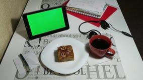 Ταμπλέτα με την πράσινη οθόνη στον καφέ και τον εξυπηρετούμενο καφέ φιλμ μικρού μήκους