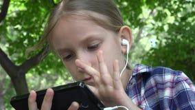 Ταμπλέτα παιχνιδιού παιδιών στην παιδική χαρά στο πάρκο, συνεδρίαση κοριτσιών στον πάγκο, Smartphone 4K απόθεμα βίντεο