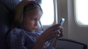Ταμπλέτα παιχνιδιού παιδιών στο αεροπλάνο, μικρό πορτρέτο κοριτσιών που χρησιμοποιεί το αεροπλάνο Smartphones απόθεμα βίντεο