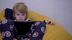 Ταμπλέτα προσοχής αγοριών καθμένος σε ένα μαξιλάρι πουφ απόθεμα βίντεο