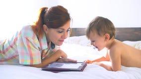 Ταμπλέτα ρολογιών Mom και γιων στην κρεβατοκάμαρα απόθεμα βίντεο