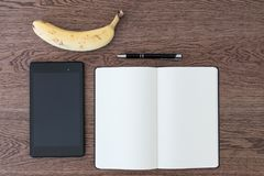Ταμπλέτα, σημειωματάριο, μάνδρα και μια μπανάνα σε έναν ξύλινο πίνακα Εικόνα συμπυκνωμένη στοκ εικόνες