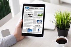 Ταμπλέτα υπολογιστών εκμετάλλευσης χεριών ατόμων με app την οθόνη παγκόσμιων ειδήσεων Στοκ Φωτογραφία