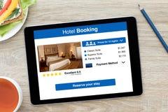 Ταμπλέτα υπολογιστών με app την κράτηση ξενοδοχείων στον ξύλινο πίνακα οθόνης Στοκ Εικόνα