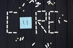 Ταμπλέτες, κάψες χαπιών και κάρτα χρώματος στη μορφή της θεραπείας λέξης Στοκ εικόνα με δικαίωμα ελεύθερης χρήσης